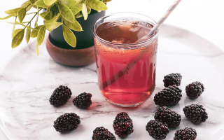 A cup on a small circular table with a health drink, a plant and blackberries on the table.