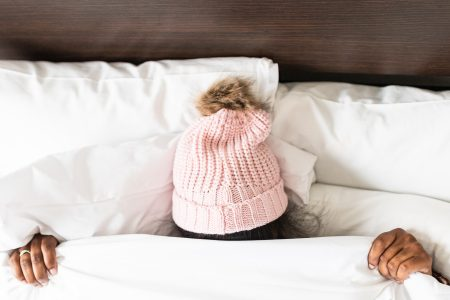 lady in bed covering herself except for the winter hat on her head.