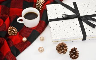 A blanket with pine cones and a cup of coffee sitting on top. Next to it is a gift wrapped box with a ribbon.