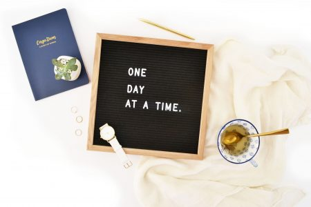 "a board with lettering that says, ""One day at a time."" Surrounded by decorative items such as tea cup with tea and a notebook"