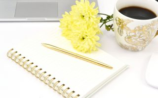 Notepad with pen on top, yellow flowers and a cup of coffee next to them.