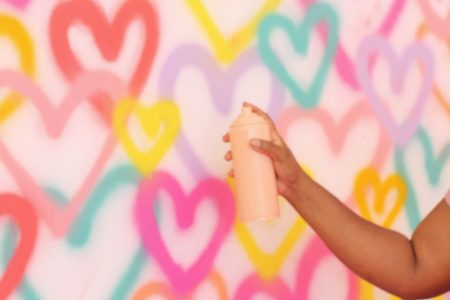 Wall of multicolored spray painted hearts.